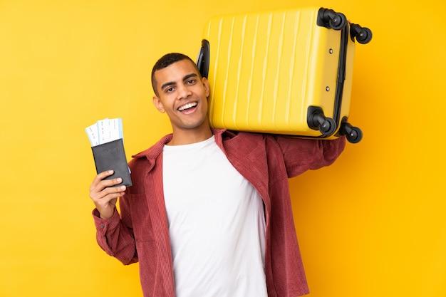 Jovem afro-americano sobre parede amarela isolada em férias com mala e passaporte