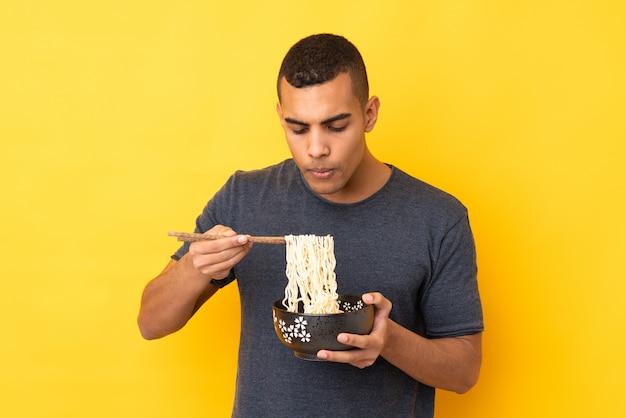 Jovem afro-americano sobre parede amarela isolada, segurando uma tigela de macarrão com areia de pauzinho, soprando, porque eles são quentes