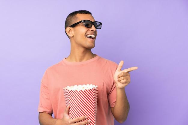 Jovem afro-americano sobre parede azul isolada com óculos 3d e segurando um grande balde de pipocas enquanto aponta a frente