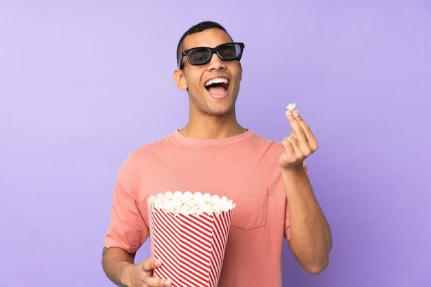 Jovem afro-americano sobre parede azul isolada com óculos 3d e segurando um grande balde de pipocas