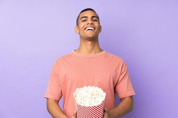 Jovem afro-americano sobre parede azul isolada, segurando um grande balde de pipocas