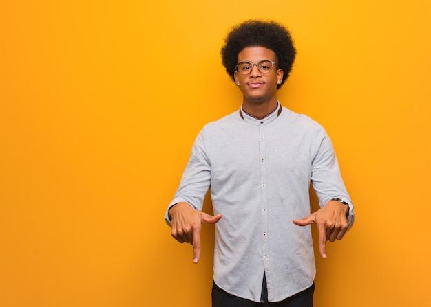 Jovem afro-americano sobre uma parede laranja, apontando para o fundo com os dedos