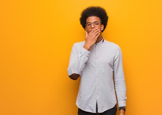 Jovem afro-americano sobre uma parede laranja cansado e com muito sono