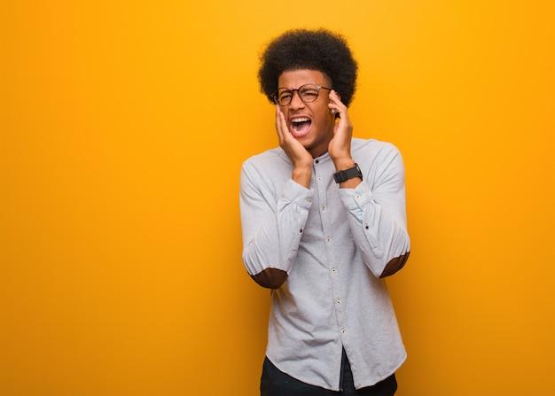 Jovem afro-americano sobre uma parede laranja desesperada e triste