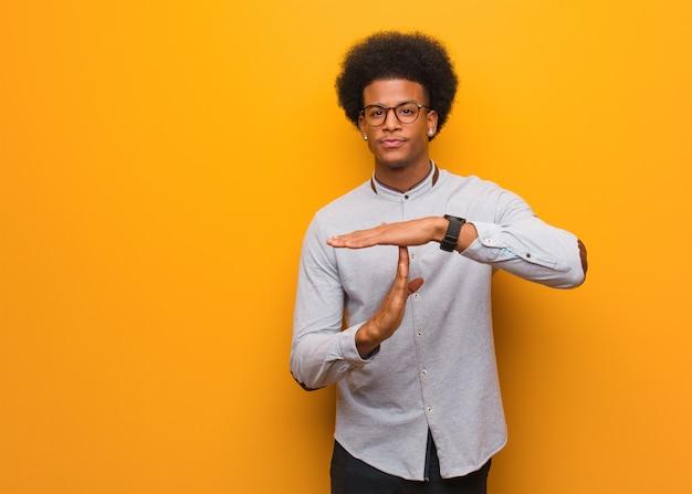 Jovem afro-americano sobre uma parede laranja, fazendo um gesto de tempo limite
