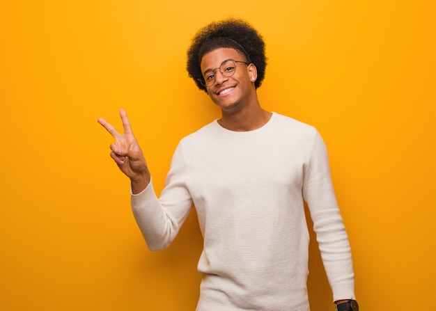 Jovem afro-americano sobre uma parede laranja, fazendo um gesto de vitória