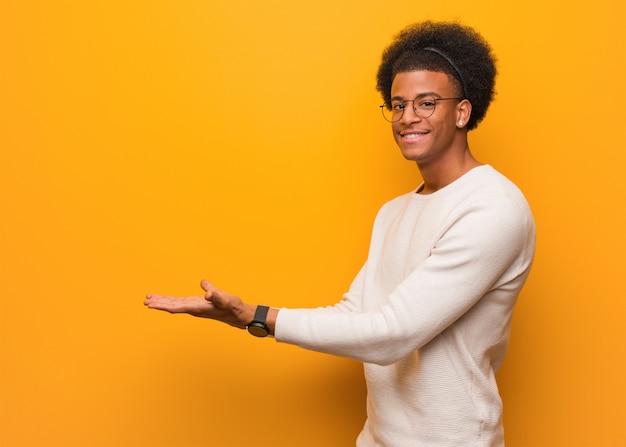 Jovem afro-americano sobre uma parede laranja segurando algo com as mãos