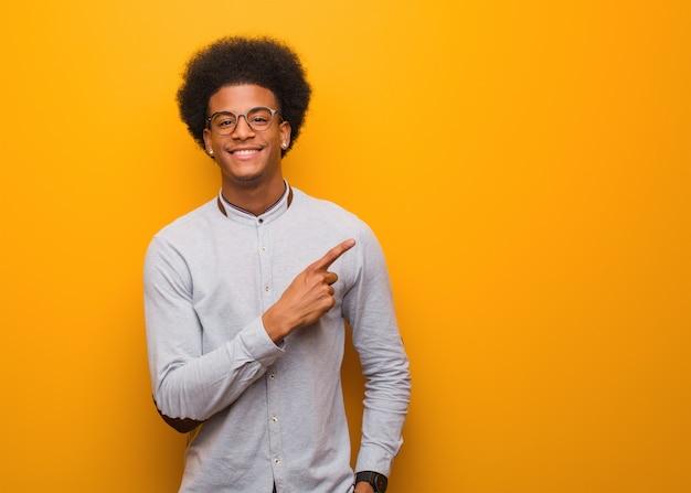 Jovem afro-americano sobre uma parede laranja, sorrindo e apontando para o lado