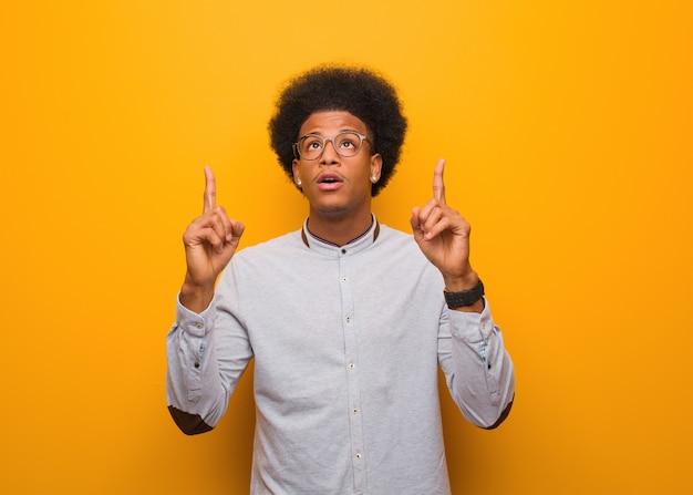 Jovem afro-americano sobre uma parede laranja surpreso apontando para cima para mostrar algo