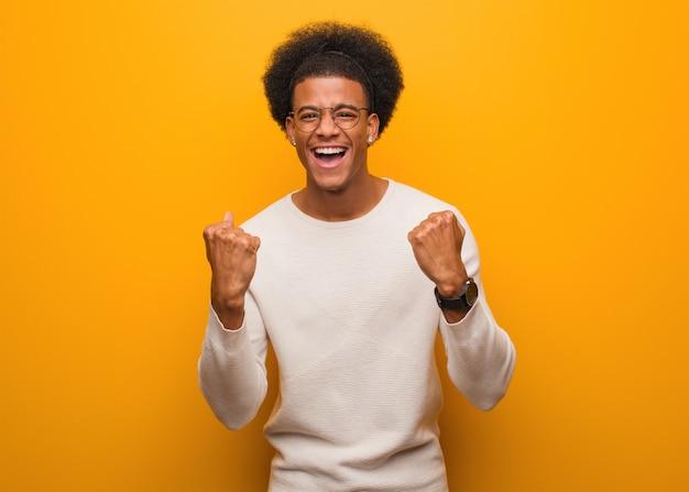 Jovem afro-americano sobre uma parede laranja surpreso e chocado