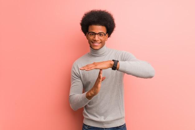 Jovem afro-americano sobre uma parede rosa, fazendo um gesto de tempo limite
