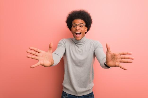 Jovem afro-americano sobre uma parede rosa muito feliz dando um abraço na frente