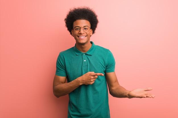 Jovem afro-americano sobre uma parede rosa segurando algo com a mão