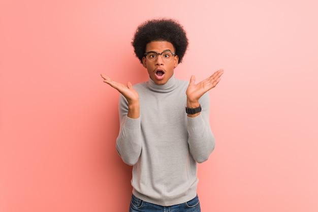 Jovem afro-americano sobre uma parede rosa surpreso e chocado