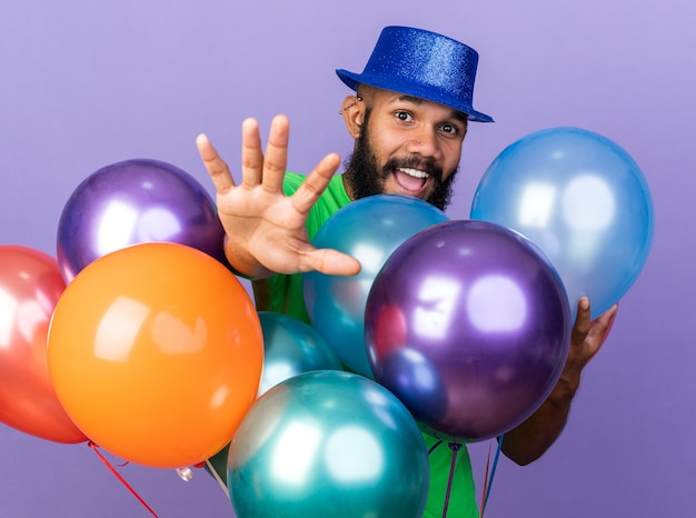Jovem afro-americano sorridente com chapéu de festa em pé atrás de balões, estendendo a mão na frente, isolado na parede azul