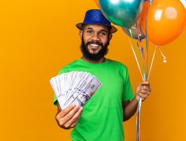 Jovem afro-americano sorridente com chapéu de festa segurando balões e dinheiro