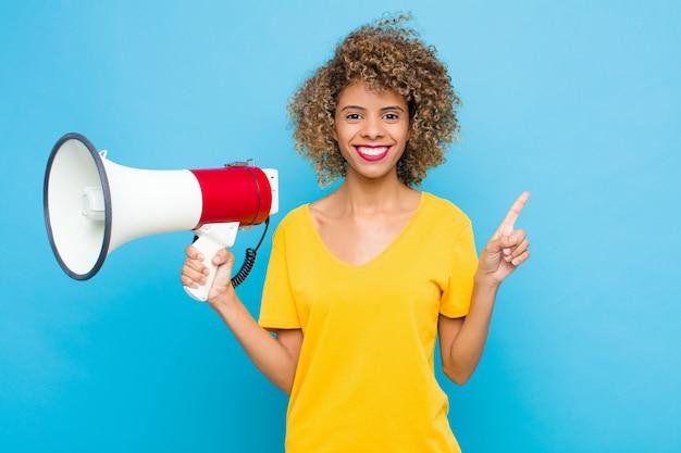 Jovem afro-americano sorrindo alegremente, sentindo-se feliz e apontando para o lado e para cima, mostrando o objeto no espaço da cópia com um megafone