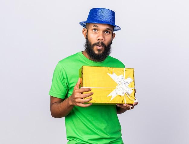 Jovem afro-americano surpreso com um chapéu de festa segurando uma caixa de presente isolada na parede branca