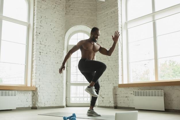 Jovem afro-americano treinando em casa, fazendo exercícios de fitness, aeróbica