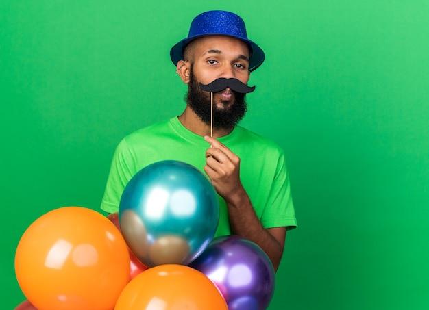 Jovem afro-americano triste com chapéu de festa segurando bigode falso em um palito isolado na parede verde