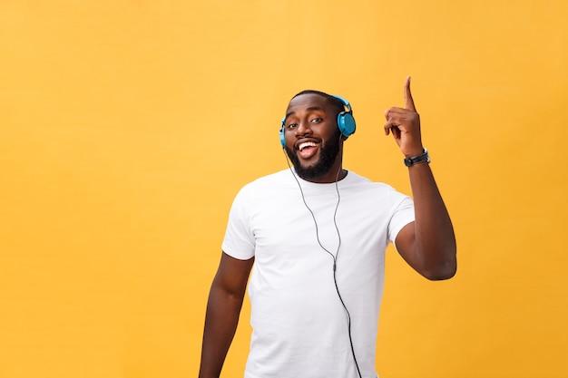 Jovem afro-americano usando fone de ouvido e curtindo música dançando