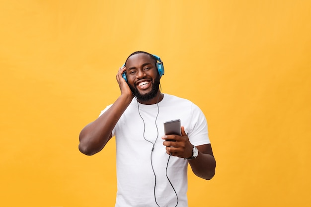 Jovem afro-americano usando fone de ouvido e curtindo música