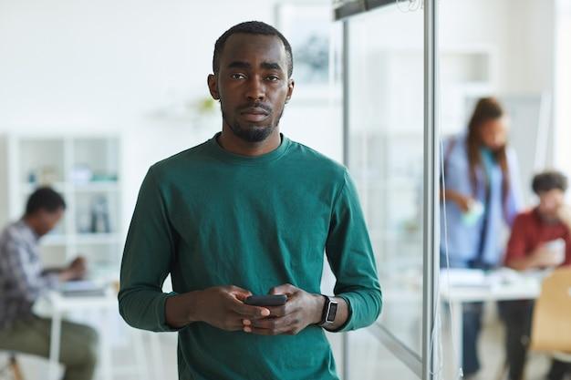 Jovem afro-americano vestido com roupas casuais e segurando um smartphone enquanto está no escritório