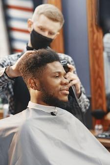 Jovem afro-americano visitando uma barbearia