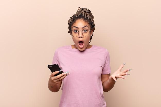 Jovem afro de boca aberta e pasma, chocada e atônita com uma surpresa inacreditável. conceito de telefone inteligente