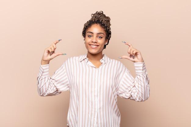 Jovem afro emoldurando ou esboçando o próprio sorriso com as duas mãos isoladas
