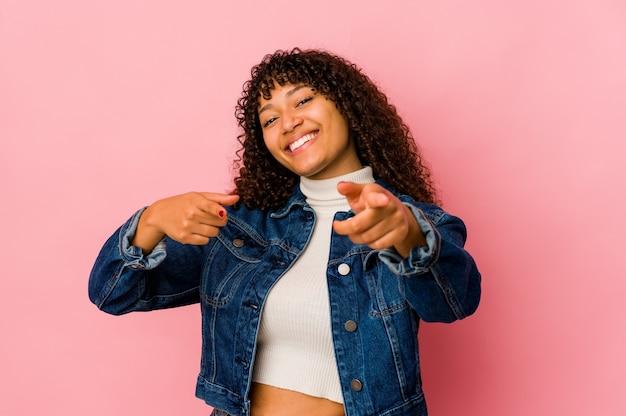 Jovem afro isolada com um sorriso alegre apontando para a frente