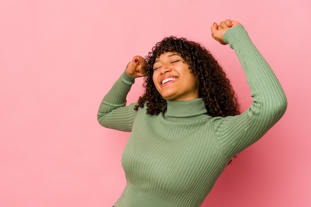 Jovem afro isolada comemorando um dia especial, pula e levanta os braços com energia