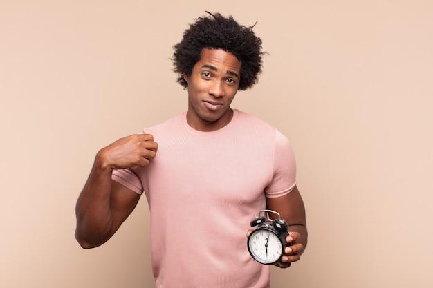 Jovem afro parecendo arrogante, bem-sucedido, positivo e orgulhoso, apontando para si mesmo