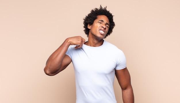 Jovem afro parecendo estressado, cansado e frustrado, secando o suor da testa, sentindo-se desesperado e exausto