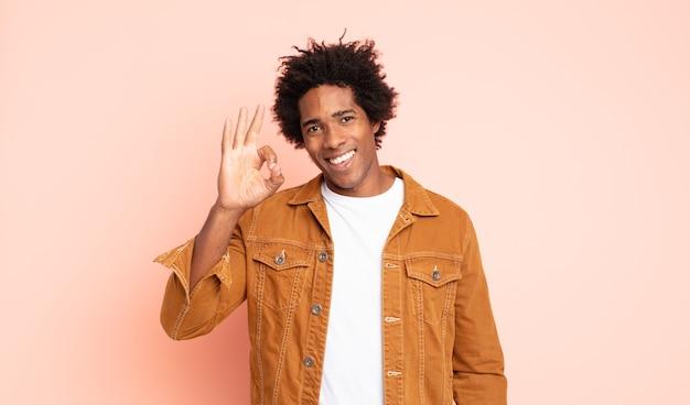 Jovem afro se sentindo feliz, relaxado e satisfeito, mostrando aprovação com gesto de ok, sorrindo