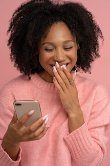 Jovem afro sorridente, olhando para o celular, rindo de uma piada, cobrindo a boca bem aberta