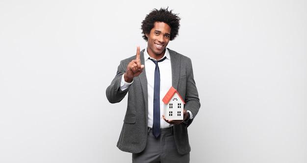 Jovem afro sorrindo com orgulho e com confiança, fazendo o número um. conceito imobiliário