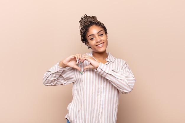 Jovem afro sorrindo e se sentindo feliz, fofa, romântica e apaixonada, fazendo formato de coração com as duas mãos