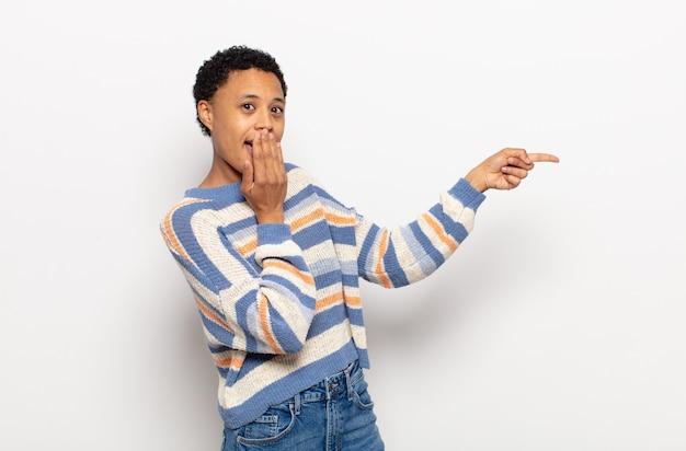 Jovem afro sorrindo feliz e olhando de soslaio, pensando, pensando ou tendo uma ideia