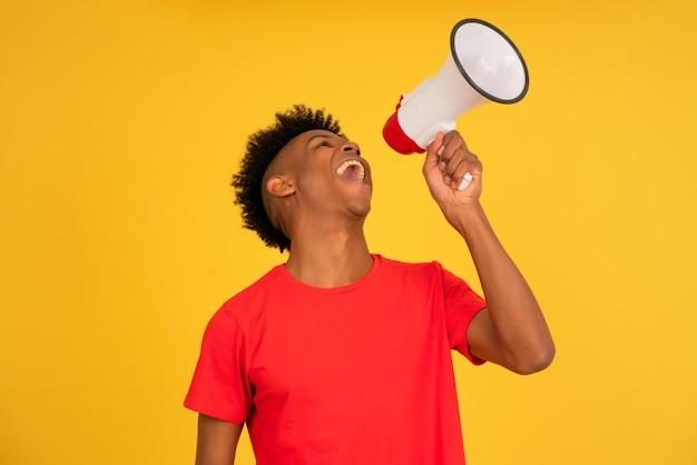Jovem afro usando um megafone para levantar a voz em pé contra um fundo amarelo. conceito de publicidade e promoção.