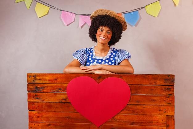Jovem afro vestida para festa junina atrás de uma placa de madeira com um coração