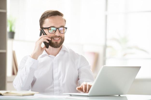 Jovem agente confiante ou corretor de consultoria em um cliente no smartphone enquanto olha para a tela do laptop na frente dele