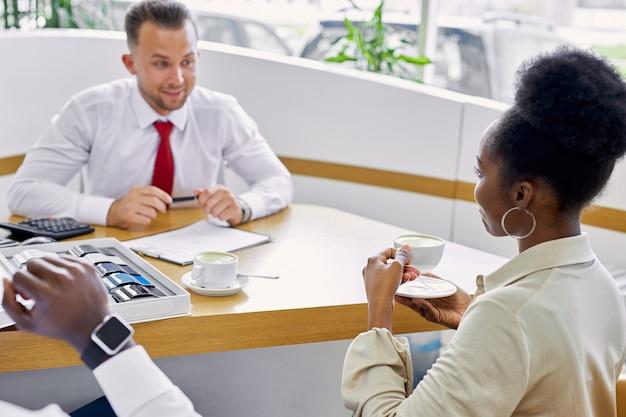 Jovem agente de vendas profissional caucasiano e clientes afro-americanos