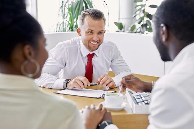 Jovem agente de vendas profissional e clientes afro-americanos