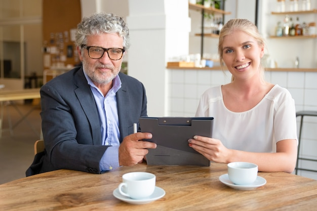 Jovem agente e cliente maduro se encontrando para tomar uma xícara de café no trabalho, sentado à mesa, segurando documentos,