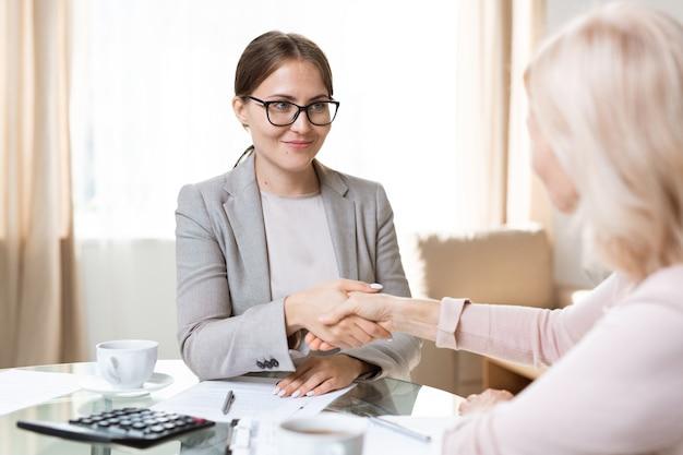 Jovem agente em trajes formais e óculos, olhando para um cliente maduro enquanto aperta sua mão após assinar papéis
