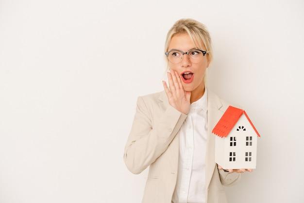 Jovem agente imobiliária segurando uma casa modelo isolada no fundo branco está contando uma notícia secreta de travagem e olhando para o lado