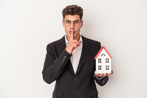 Jovem agente imobiliário caucasiano isolado no fundo branco, mantendo um segredo ou pedindo silêncio.