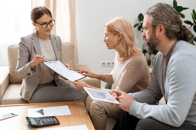 Jovem agente imobiliário com documento apontando a soma das despesas financeiras enquanto consulta casal maduro em reunião