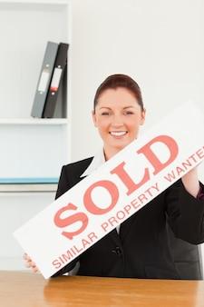 Jovem agente imobiliário segurando um cartaz vendido